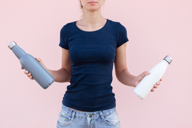 young-girl-holding-two-reusable-steel-thermo-water-bottles-white-grey-colors-pastel-pink-background-be-plastic-free-zero-waste.jpg